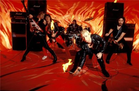 Judas Priest studio red flames background flaming microphone and guitars LONDON, 1981